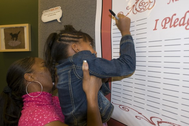 Jania Young, 7, signs a Red Ribbon Week proclamation to live a drug-free life during an Oct. 22 ceremony at the 81st Regional Support Command located at Fort Jackson. S.C. Jania is the daughter of Audrey Young, who is a Yellow Ribbon Reintegration Program specialist with the 81st RSC