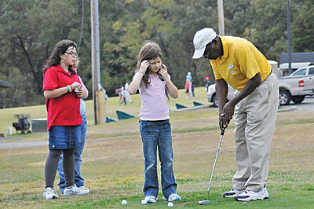 Georgia Kauble Horton, 4th grader, listens as Henry Parham, First Tee golf coach, explains to her how to hold the putter and position her body while putting Tuesday afternoon at Cole Park Commons. The First Tee program teaches school age children basic golf skills and nine core values to apply to all aspects of their every day life.