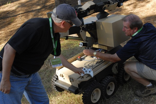 """Mr. Brian Hart, left, and Mr. Bob Hughes, representatives of Black-I Robotics Inc., showcase the """"Land Shark"""" on Friday during the event's Extravaganza portion. Users can operate the robot with an Xbox 360 game controller, seen held by Mr."""
