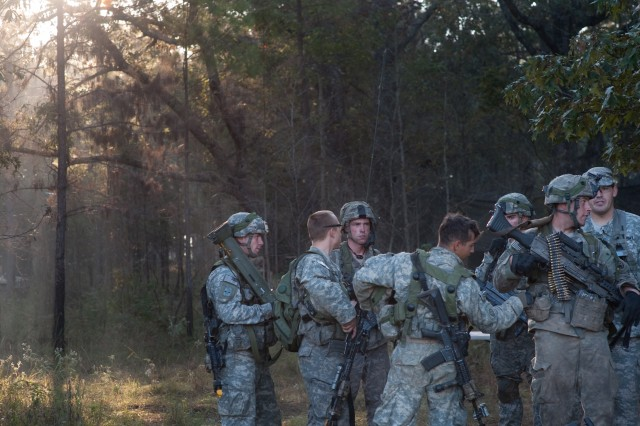 "Soldiers huddle up during a ""tactical freeze"" portion of the Full Spectrum Operation exercise in Ft. Polk, LA, Saturday, Oct. 23, 2010.  The Full Spectrum exercise focuses on facing and defeating a hybrid threat representing both an insurgent force and an organized military force."