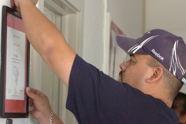FORT BLISS, Texas (October 23, 2010) Angel Jimenez, a civil engineer with Fort Bliss Directorate of Public Works, hangs a plaque on the wall of the American Red Cross association on post, Oct. 23. Jimenez and other DPW employees volunteered to clean, move furniture and spruce up the building for Make a Difference Day.