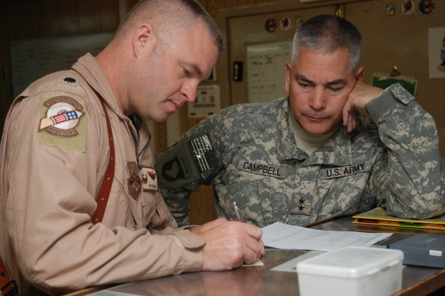 BAGRAM AIRFIELD, Afghanistan - U.S. Army Maj. Gen. John F. Campbell, Combined Joint Task Force 101, Regional Command East commander, receives an initial briefing for an upcoming flight on an F-15E Strike Eagle from U.S. Air Force Lt. Col. Allan A. Nilles, 336th Expeditionary Fighter Squadron commander, Oct. 20. Campbell is flying with members of the Strike Eagle squadron to become more familiar with the mission and capabilities of the F-15 which provides close-air support to his Soldiers on the ground in eastern Afghanistan.  (Photo by U.S. Air Force Tech. Sgt. M. Erick Reynolds, Regional Command East Public Affairs)
