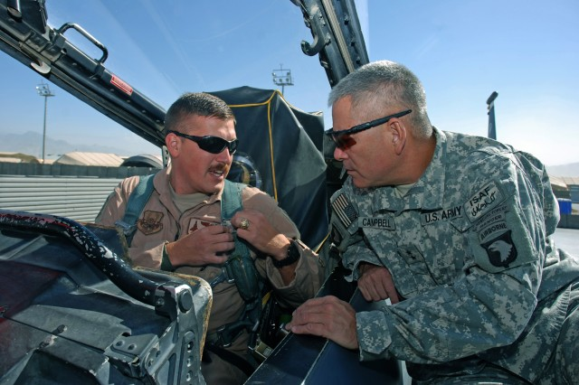 BAGRAM AIRFIELD, Afghanistan - U.S. Air Force Capt. Ross E. Clark, 336th Expeditionary Fighter Squadron F-15 weapons systems officer, demonstrates to U.S. Army Maj. Gen. John F. Campbell, Combined Joint Task Force 101, Regional Command East commander, the proper attachment of the parachute harness to the ejection system of the F-15E Strike Eagle Oct 20. Campbell is scheduled to fly with members of the F-15 squadron to become more familiar with the mission and capabilities of the Strike Eagle, which provides close-air support to his Soldiers on the ground in eastern Afghanistan. (Photo by U.S. Air Force Tech. Sgt. M. Erick Reynolds, Regional Command East Public Affairs)