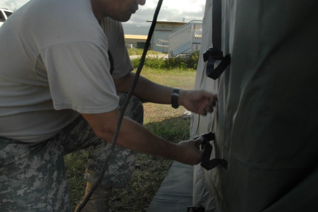 MARINE CORPS BASE HAWAII, (Kaneohe) Hawaii- Col. Marlin Remigio, U.S. Army, Pacific Contingency Command Post advanced party officer in charge, assembles a tent at the field training site of the CCP's Validation Exercise to provide shelter for Soldiers during the training.