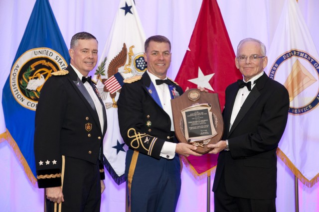 Col. Theodore Harrison (center), former commander of the 410th Contracting Support Brigade, Fort Sam Houston, Texas, accepts his award as the Acquisition Director of the Year Colonel Level from, Lt. Gen. William N. Phillips, Principal Military Deputy, Office of the Assistant Secretary for Acquisition, Logistics and Technology and the Honorable Malcolm Ross O'Neill, Assistant Secretary of the Army for Acquisition, Logistics and Technology.