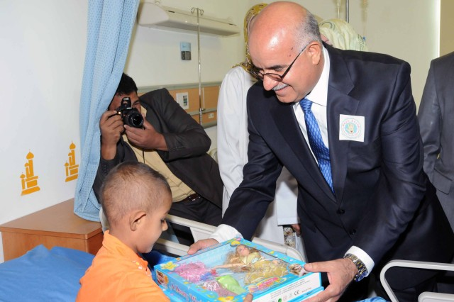 Dr. Salih Mahdi, Iraq's minister of health, gives an Iraqi girl a gift at the new Basra Children's Hospital Oct. 21. Mahdi went from room-to-room, greeting kids and looking at the children's medical charts.