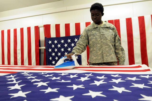 Pfc. Antwonette McFadden, an Augusta, Ga., native irons an American flag to cover the transfer case of a fallen servicemember at Kandahar Airfield, Afghanistan, Oct. 25. It takes approximately 45 minutes to iron a single flag by hand.