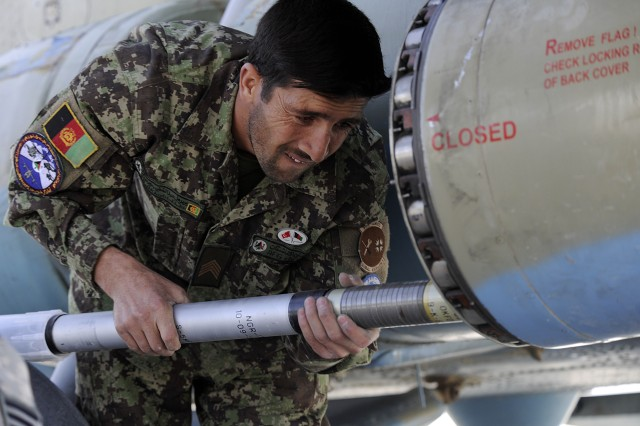 A member of the Afghan National Army Air Force's 305th Aircraft Maintenance Squadron loads a 57mm rocket into Russian MI-17 helicopter's rocket pod Oct. 20 before flying an escort mission.