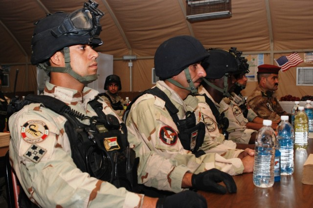 Maj. Ryad Hadi, far right, sits with the Basra Special Weapons and Tactics team before their graduation ceremony at the Basra Operations Center Oct. 18. The SWAT team has spent weeks training on weapons, tactics and drills to become trainers for the Basra Police Force.