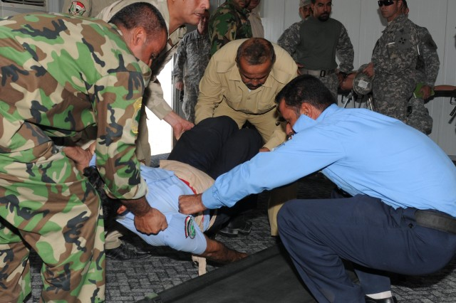 Four Department of Border Enforcement workers train to lift an injured victim onto a stretcher at the Shaiba Training Center Oct. 13 while United States Division-South officials observe the training. USD-S Soldiers facilitated several months of discussions between the Iraqi Army and DBE to conduct the course for the DBE workers.
