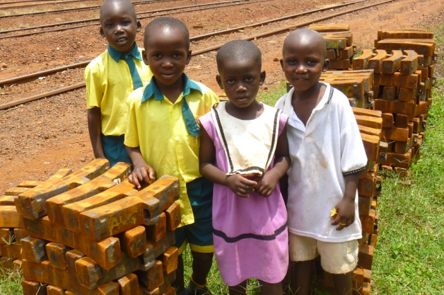Children gather for a photo at the railway station, Jinja, Uganda, Sept. 14, 2010. U.S. Army Africa and SDDC Transportation Engineering Agency logisticians supported a Uganda People's Defense Force team to determine the current operational status of the Ugandan railway system and its rolling stock, assess the capability of UPDF personnel to rehabilitate the network, and identify potential sites for training and repair operations. A five-year reconstruction of the nation's railway system is in the planning stages.