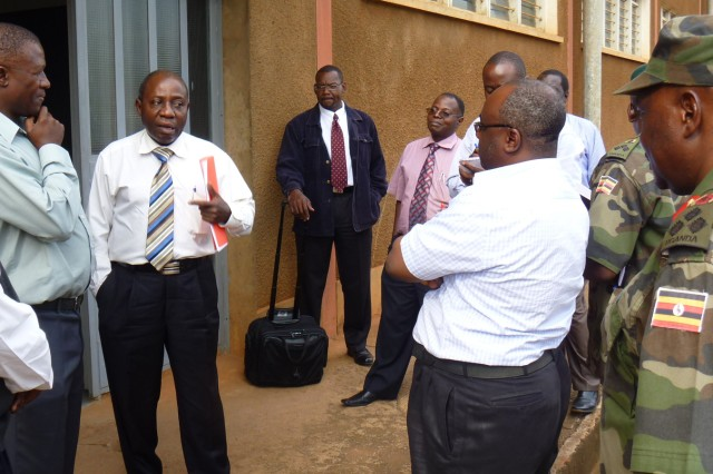Augustine O. Mugisa (second from left), Uganda Ministry of Works and Transport, speaks with assessment team colleagues during a tour of the Nalakolongo Railway Repair Facility, Kampala, Nigeria, Sept. 13, 2010.  Lloyd Coakley, Military Surface Deployment and Distribution Command Transportation Engineering Agency is at rear center with suitcase. Coakley and U.S. Army Africa logistician John Hanson supported a Uganda People's Defense Force team to determine the current operational status of the Ugandan railway system and its rolling stock, assess the capability of UPDF personnel to rehabilitate the network, and identify potential sites for training and repair operations. A five-year reconstruction of the nation's railway system is in the planning stages.