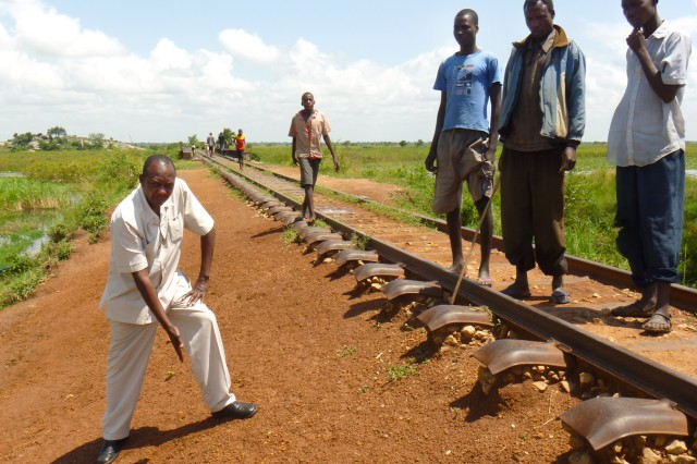 Lt. Col. Luke Arikosi, Uganda People's Defense Force, points to the high water mark on a section of track near Kumi, Uganda, Sept. 15, 2010. U.S. Army Africa and SDDC Transportation Engineering Agency logisticians supported a Uganda People's Defense Force team to determine the current operational status of the Ugandan railway system and its rolling stock, assess the capability of UPDF personnel to rehabilitate the network, and identify potential sites for training and repair operations. A five-year reconstruction of the nation's railway system is in the planning stages.