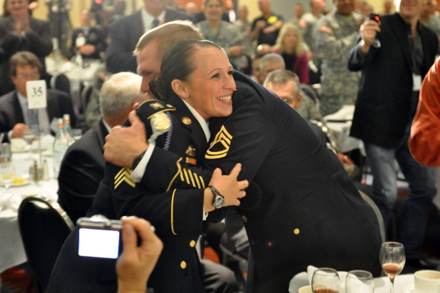 WASHINGTON -- Sgt. Sherri Jo Gallagher, U.S. Army Marksmanship Unit, receives a hug from Sgt. 1st Class David Steinbach moments after Sgt. Maj. of the Army Kenneth O. Preston announced that she was the 2010 Army Soldier of the Year Monday. Steinbach was Gallagher\'s sponsor and trained with Gallagher to prepare her for the rugged Army Best Warrior Competition last week at Ft. Lee, Va. (Photo by Michael Molinaro, USAMU PAO)