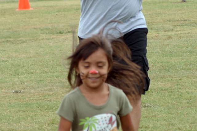 "FORT HOOD, Texas-Staff Sgt. Francisco Toledo, a technical inspector with =3rd Assault Helicopter Battalion, 227th Aviation Regiment, 1st Air Cavalry Brigade, 1st Cavalry Division, runs with his daughter, Arianna, toward the finish line during a ""kids physical fitness training"" session in Killeen, Texas Oct. 23. The event was held in conjunction with a food drive to benefit the Cove House, a non-profit ministry that provides food and shelter to the homeless in Copperas Cove, Texas."