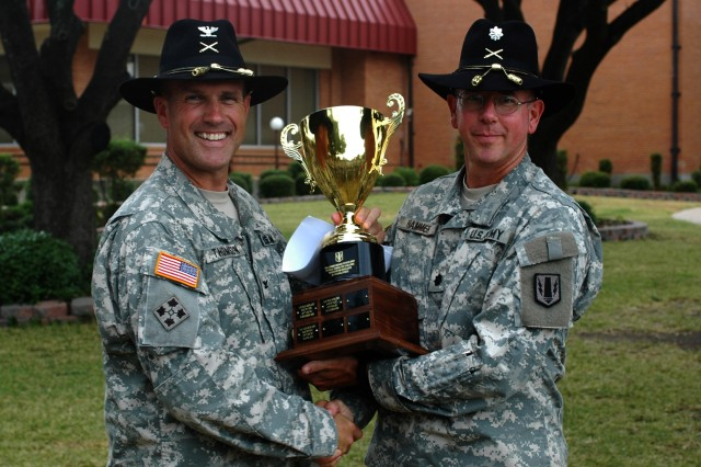 FORT HOOD, Texas- Col. John Thomson (left), brigade commander of the 41st Fires Brigade, presents a first place trophy to Lt. Col Brian Hammer, battalion commander of the 2nd Battalion, 20th Field Artillery Regiment, 41st Fires Brigade, for his battalion winning the third annual officer APFT Challenge with an average score of 282.1 on the extended scale.