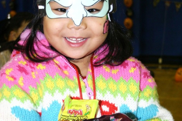 A kindergarten student from Dongurami smiles after collecting a handful of candy during a party thrown by 17th Ordnance Company Soldiers for children at the Red Cloud Garrison gym Oct. 26.