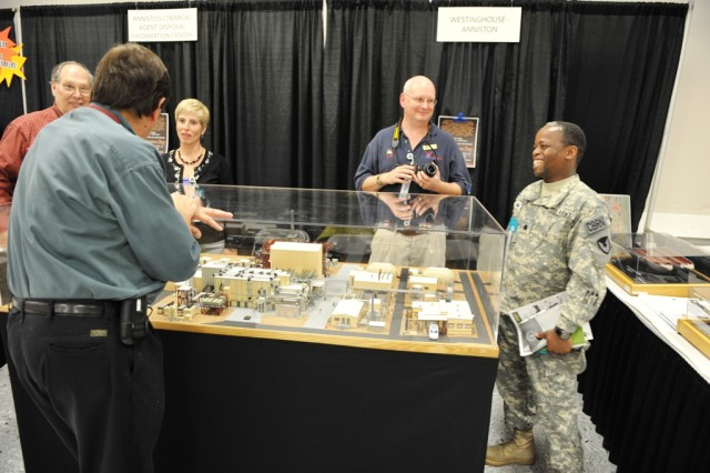 Lt. Col. Will Flucker, commander of Anniston Chemical Activity speaks with employees at the Anniston Chemical Agent Disposal Facility display at the Calhoun County Chamber of Commerce's Business to Business Expo.