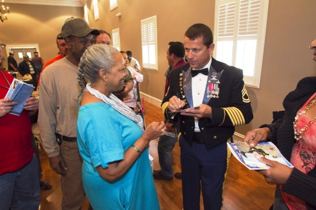 Retired Sgt. First Class Dana Bowman signs an autograph for Anniston Army Depot's Marciann Manley following the depot's Disability Awareness Month luncheon Oct. 20.