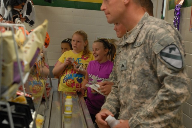BELTON, Texas- Kalamazoo, Mich. native, Sgt. Jeremy Pelletier, a forward observer with 2nd Battalion, 5th Cavalry Regiment, 1st Brigade Combat Team, 1st Cavalry Division, waits in the lunch line with the students from Leon Heights Elementary School as part of the Adopt-A-School Program, here, Oct. 27.