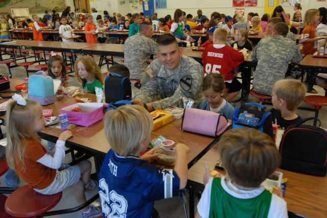 BELTON, Texas- San Antonio native, 2nd Lt. Ronald Youngblood, a fire support officer with 2nd Battalion, 5th Cavalry Regiment, 1st Brigade Combat Team, 1st Cavalry Division, eats his lunch with students of Leon Heights Elementary School as part of the Adopt-A-School Program, Oct. 27.