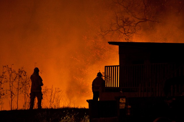 Firefighters were silhouetted by the fire that raged around the urban training center on the range complex.