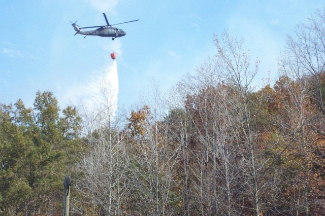 The red Bambi bucket is visible as the Blackhawk maneuvered their drops as the fire team personnel guided them from the ground.