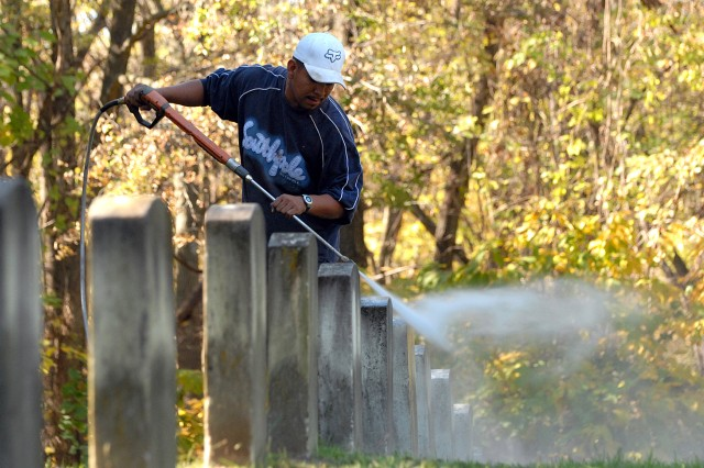 Al Morales power-washes headstones in the U.S. Disciplinary Barracks Cemetery Oct. 21 at Fort Leavenworth, Kan. Workers also volunteered to straighten the headstones.