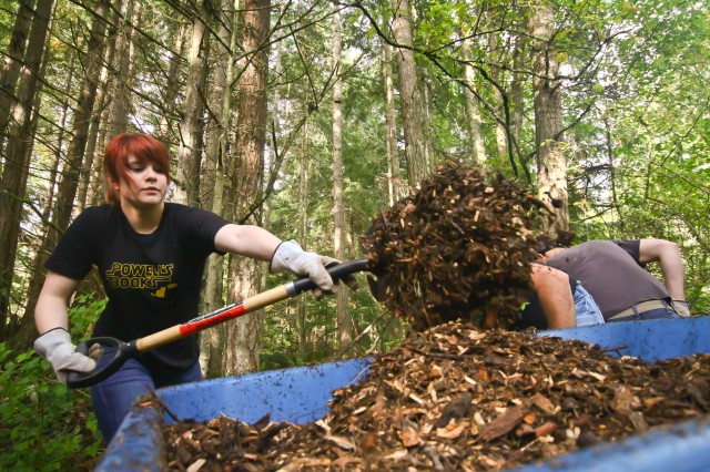 (left) Pfc. Evelyn Goldsmith, a computer specialist with the 51st Signal Battalion, loads a wheel barrow with wood chips to spread on a trail in Farrell Marsh Park, Steilacoom Oct. 22.  Goldsmith and 26 other volunteers from the 42nd Military Police Brigade participated in the trail renovation during the 20th annual Make a Difference Day. (U.S. Army photo/Capt. Michael Greenberger)