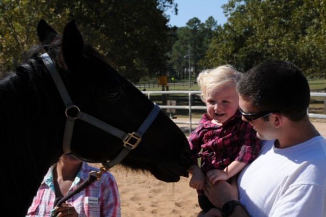 Brandon Lee and his daughter, Olivia, 19 months, visit with Smokey the horse.
