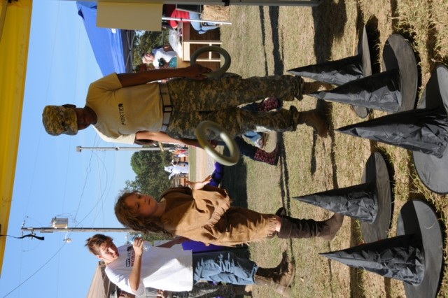 WOC Asha Porter assists Emily Marcoux, 9, with a ring toss during the Terrorific Children's Festival. For more event photos, visit the Army Flier Facebook page.