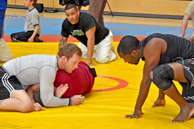 Service members look on as UFC fighter Gray Maynard demonstrates fighting techniques during a visit to Wiesbaden.