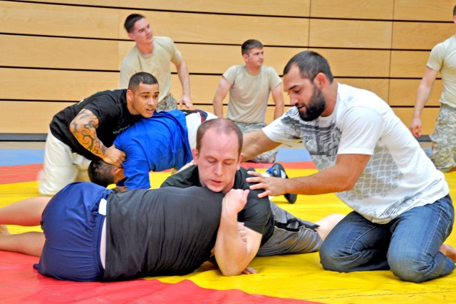 The UFC's Johny Hendricks demonstrates fighting techniques to Wiesbaden military community members during a clinic in the Wiesbaden Fitness Center.