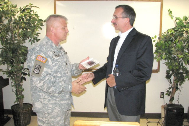 Chap. (Lt. Col.) Robert Phillips, U.S. Army Garrison (USAG) garrison chaplain, presents a parting gift to Scott Randazza, director of finance for the Coca-Cola Company, following Randazza's speech Oct. 19 at the USAG Chaplain Office leadership luncheon at the Fort McPherson Chapel Center. Randazza spoke of how his professional and personal experiences helped him to define his leadership principles, and encouraged audience members to use their natural gifts to become good leaders.