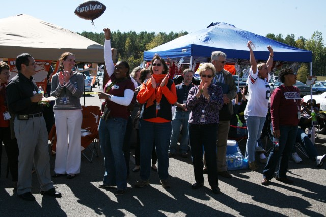 Employees from the U.S. Army Space and Missile Defense Command/Army Forces Strategic Command G8 (finance) office show their excitement for being selected as the Best Display Group during the Tailgate Party and Car Show Oct. 21.