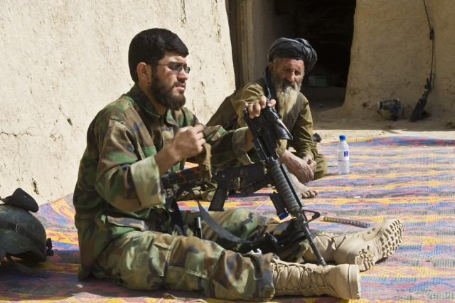 An Afghan man observes as a Soldier with 3rd Commando Kandak disassembles and cleans his M4 carbine rifle during an operation to rid insurgents from Panjwa'i District, Oct. 26, 2010, in Kandahar Province, Afghanistan. (U.S. Army photo by Spc. Daniel P. Shook/Special Operations Task Force - South).