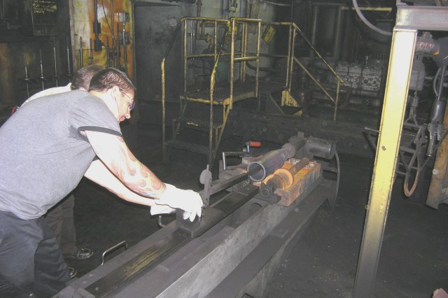 At SCAAP-Below ground, a projectile part is periodically chosen from the conveyor by an inspector who uses calipers to measure the length and width of various points on the part according to specifications and keeps exacting records of his findings.