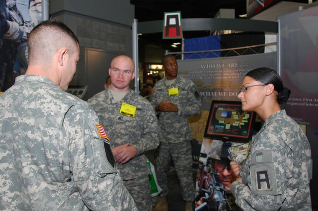 Sgt. Kevin Jarvis (second from left), 166th Aviation Brigade, First Army Division West, and Spc. Ashley Killian (center), 188th Infantry Brigade, First Army Division East, talk with Soldiers at the Association of the United States Army (AUSA) Annual Meeting and Exposition in Washington, D.C., Oct 25. The three-day event at the Walter E. Washington Convention Center brought thousands of Soldiers, DA Civilian employees and defense contractors together to showcase Army programs, services and equipment. Jarvis, First Army Soldier of the Year, and Killian, the runner-up, informed attendees about First Army's mission in mobilizing, training and deploying Reserve-component Soldiers.