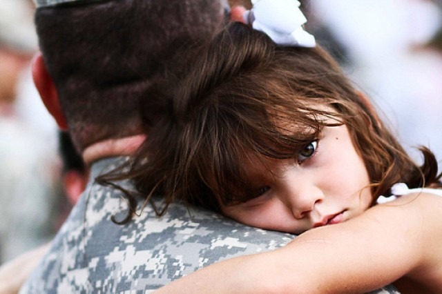 Five-year-old Maddie Lovell, right, clings to her father, U.S. Army Sgt. 1st Class Jacob Lovell, of 585th Military Police Company, during a welcome home ceremony, at Marysville High School, in Marysville, Ohio, Aug. 13, 2010.