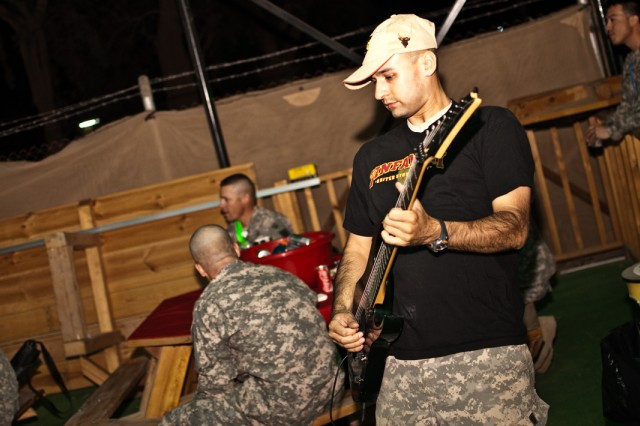 Staff Sgt. Gregory Hyson, lead guitarist for Controlled Detonation, the 1st Infantry Division's official rock band, plays a riff for troops on Camp Taji, Iraq, Oct. 30. Controlled Detonation is the last Army band of its type in Iraq, and frequently tours the country to perform for service members. On their latest tour, the band performed for troops with the Enhanced Combat Aviation Brigade, 1st Infantry Division. (U.S. Army photo by Spc. Roland Hale, eCAB, 1st Inf. Div. PAO)
