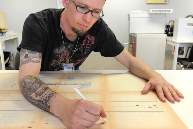 Army veteran Walter Sinnott smooths creases in a long-folded chart and map that contains details about where and at what depths specific artifacts were recovered at a U.S. Army Corps of Engineers construction site decades ago. Sinnott used accepted archiving and curation techniques to unfold the chart without further damaging it. He will also make necessary repairs to the document before deciding how best to curate and preserve it for future historians and researchers.