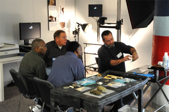 Digital imagery skills are necessary to record accurate, properly lighted photos of artifacts. The images become valuable records made available online to researchers and other interested parties. Here, contract photographer Dave Knoerlein (right), a professional forensic photographer hired for the program, discusses the details and nuances of properly photographing artifacts.