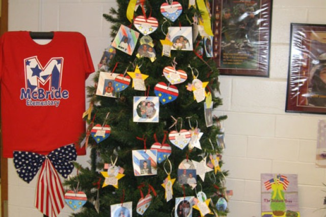 "At Fort Benning, Ga., visitors who step inside McBride Elementary School feel a heroes' welcome. The school's ""Our Heroes' Tree,"" adorned with the names and faces of the school's beloved military Families, stands proudly in the school foyer. Lisa Harman, motivated by her patriotic passion as an Army spouse, Army parent and Department of Defense Dependent Schools teacher, introduced Our Heroes' Tree to the McBride community four years ago."