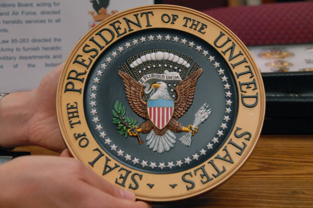 The official Presidential Seal is designed and manufactured by The Institute of Heraldry. The eagle is hand painted; the stars and clouds represent the original 13 colonies; and the olive branch and arrows represent peace and defense, respectively.