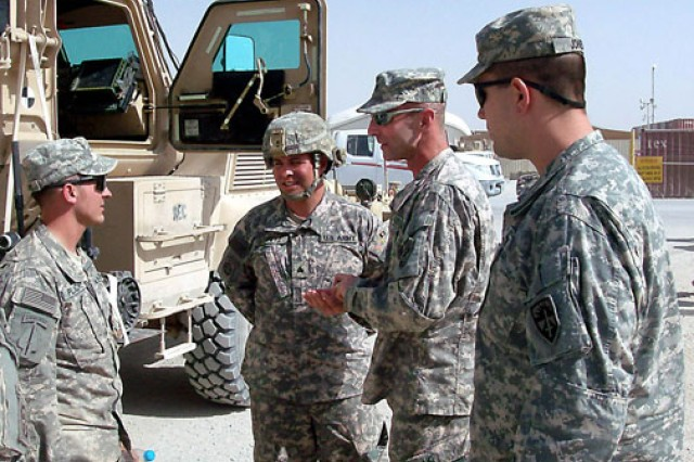Col. Brian Dosa, second from right, FOA Team XIII commander and the Operational Test Command Maneuver and Maneuver Support test director, prepares to award coins of excellence to members of a route clearance team from the 82nd Airborne Division. Maj. Brian Jones, far right, of OTC's Battle Command and Communication Test Directorate, looks on.