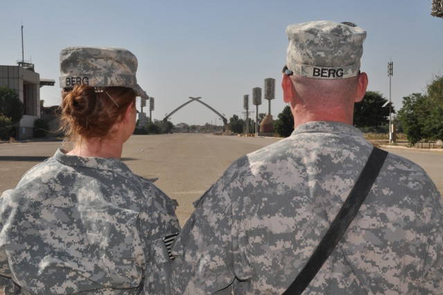 """Sgt. Ashleigh Berg (left), noncommissioned officer-in-charge of the secretary of general staff for 1st Armored Division headquarters, United States Division - Center, and a Malibu, Calif., native, and Sgt. Matthew Berg, Ashleigh's husband and a vehicle maintenance noncommissioned officer with the headquarters motor pool with 1st Armored Division, and a Mobile, Ala. native, take a moment to look at the """"Crossed Sabers"""" before reenlisting Oct. 21 in Baghdad's Green Zone."""