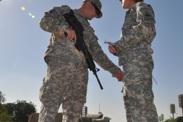"""Sgt. Matthew Berg (left), a vehicle maintenance noncommissioned officer with the headquarters motor pool with 1st Armored Division, United States Division - Center, and a Mobile, Ala., native, takes a moment to fix the pockets on the uniform of Sgt. Ashleigh Berg, his wife and noncommissioned officer-in-charge of the secretary of general staff for 1st Armd. Div., and a Malibu, Calif., native, Oct. 21 before reenlisting in front of the """"Crossed Sabers"""" in Baghdad's Green Zone."""
