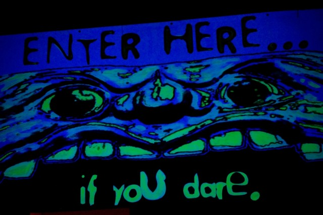 "The ominous black-light sign was the first sight of ""Theatrical Nightmare: A Walk in the Dark"" at Shoreline Park, Oct. 28-30. The production was run by the B.O.S.S program of JBLM.  (Photo by Sgt. Dayan Neely, 19th Public Affairs Detachment.)"
