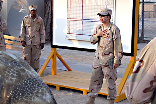 Chia Wei Lee, systems engineer for the 2nd Battalion, 401st Army Field Support Brigade, provides Joint Operations Board implementation training to Navy and ITT contractors just outside the wash rack facilities at Camp Arifjan, Kuwait.  (Courtesy photo)