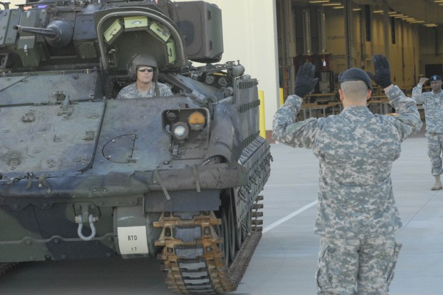 SFC Rob Putzer, of the 194th Armored Brigade's advance party, drives the first Bradley that arrived Oct. 22 into the new maintenance instruction facility at Harmony Church.